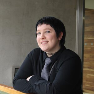 A photo of the author, a young white woman with dyed black hair and blue-grey eyes, wearing a black shirt and grey tie, smiling at the camera.